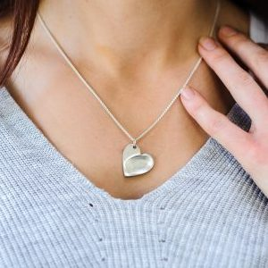 Woman wearing silver necklace with fingerprint pattern