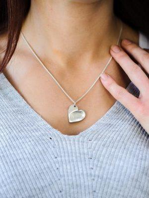 Woman wearing silver necklace with fingerprint pattern